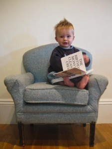 Reading a book in his very own chair!